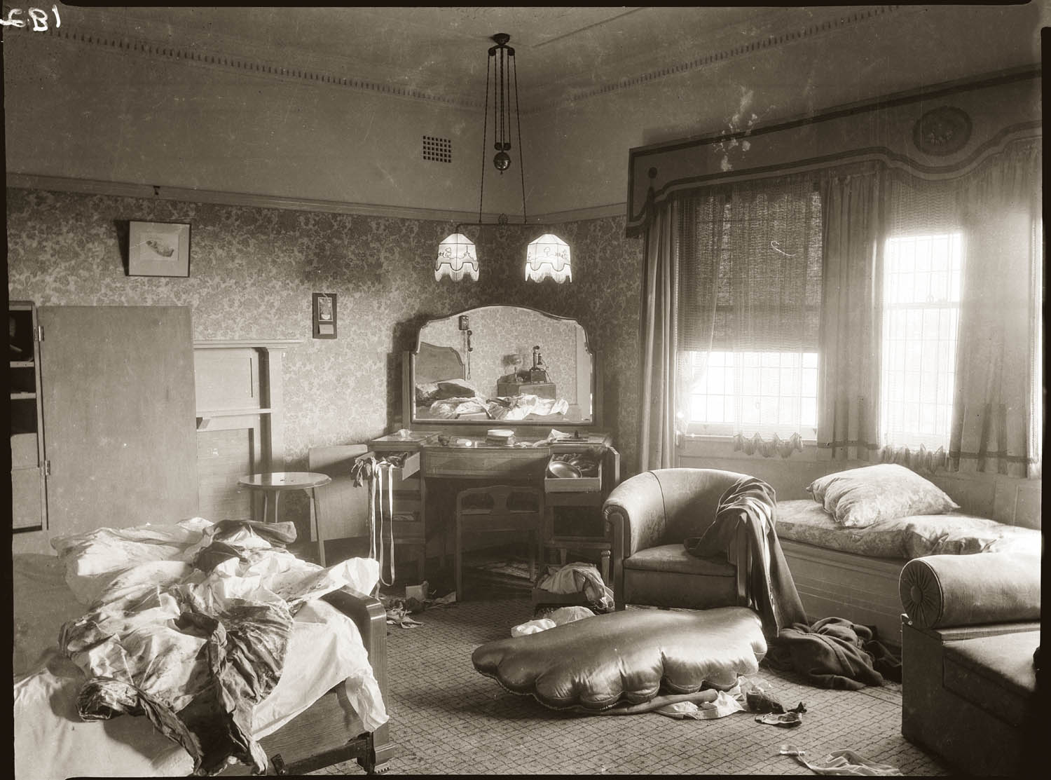 Bedroom, with bloodstained bed reflected in dressing table mirror. Details unknown, late 1930s.