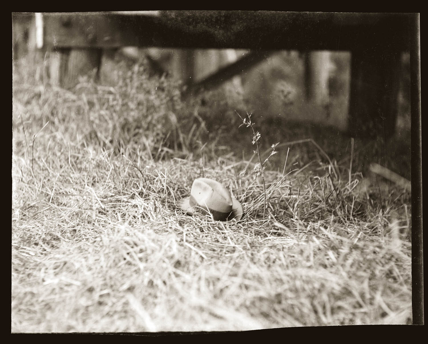 Man's hat lying on grass, beneath wooden bridge. Details unknown, early 1940s